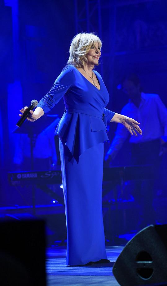 V modrých šatech jí to moc slušelo.