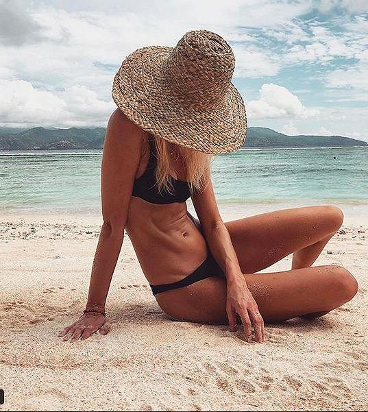 Topmodelka pózuje na pláži.