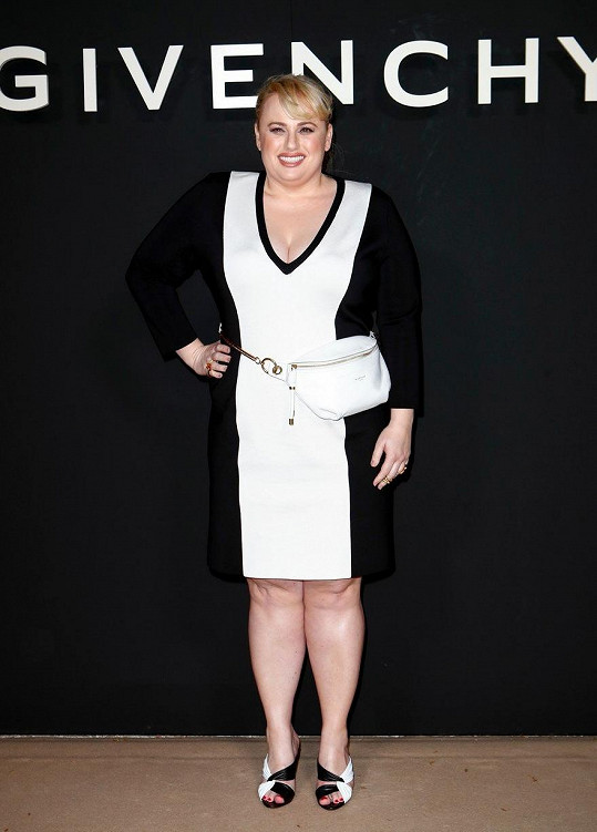 V černobílých šatech, které jí opticky zúžily pozadí.