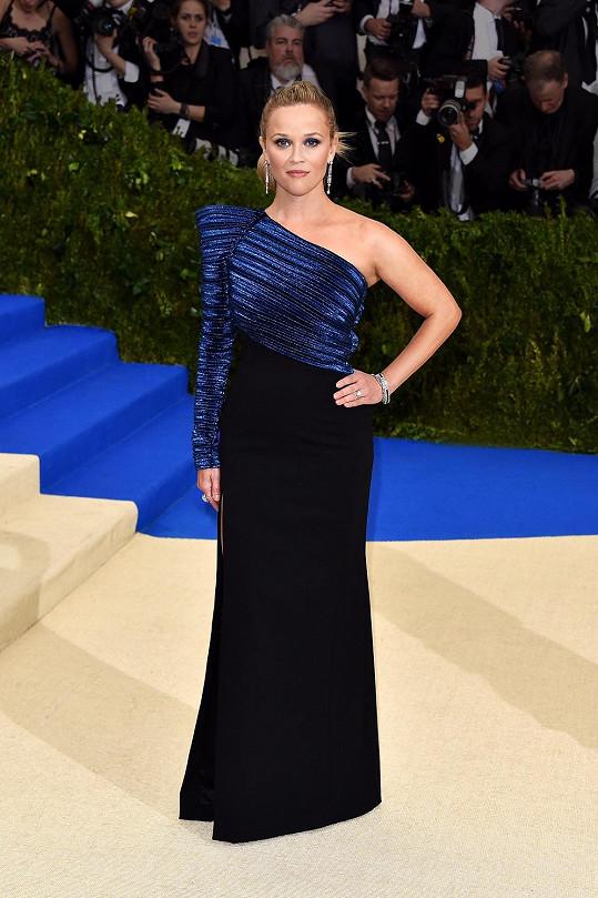 Reese Witherspoon má na sobě modro-černou róbu Mugler se strukturovaně řešeným živůtkem přes jedno rameno, s dlouhými štíhlými náušnicemi a prstenem Tiffany & Co. a sandály Jimmy Choo.