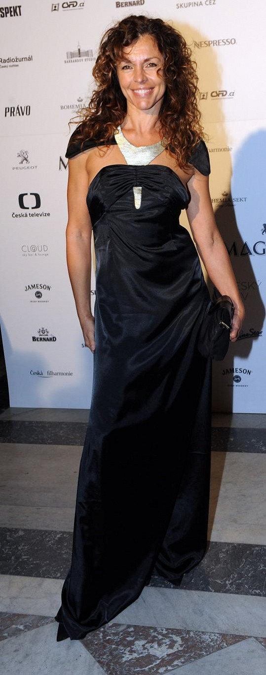 Tyto šaty se zajímavě řešenou aplikací v živůtku patří mezi ty méně hrozné ze dvou, které herečka ten večer oblékla. Při pohledu na její lesklý obličej bych ale odhadoval, že snad smažila celý den langoše.