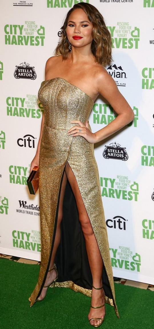 Chrissy Teigen na akci organizace City Harvest. Modelka si potrpí na šaty s vysokými rozparky.