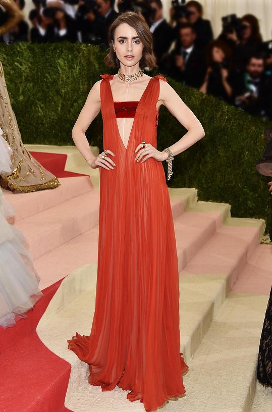 Barva šatů Lily Collins byla sice typická pro módní dům Valentino, ale střih překvapoval svou jedinečností, díky celostnímu plisování a bordó vsadce v živůtku. Herečka doplnila look šperky ze žlutého zlata od Tiffany&Co.