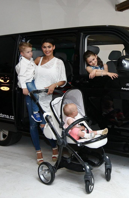 Rodinka s půjčeným miminkem pózovala u auta.