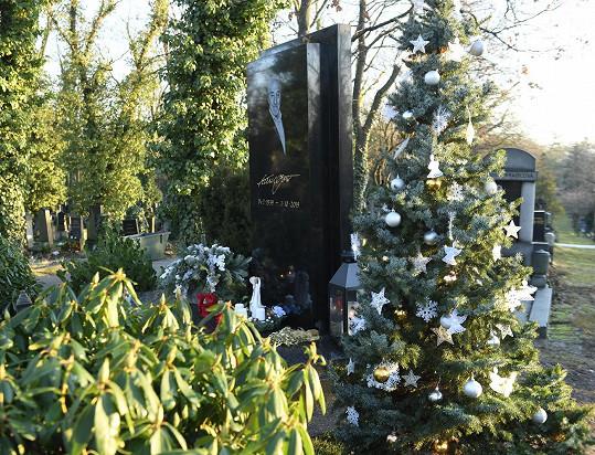 Vedle hrobu je i vánočně ozdobený stromeček.