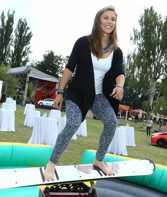 Vyzkoušela si rovnováhu na připraveném snowboardovém trenažéru.
