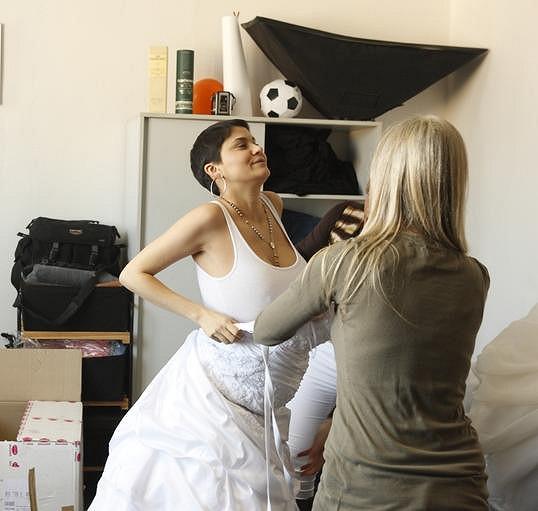 Těhulka se pokouší obléct těsné svatební šaty.