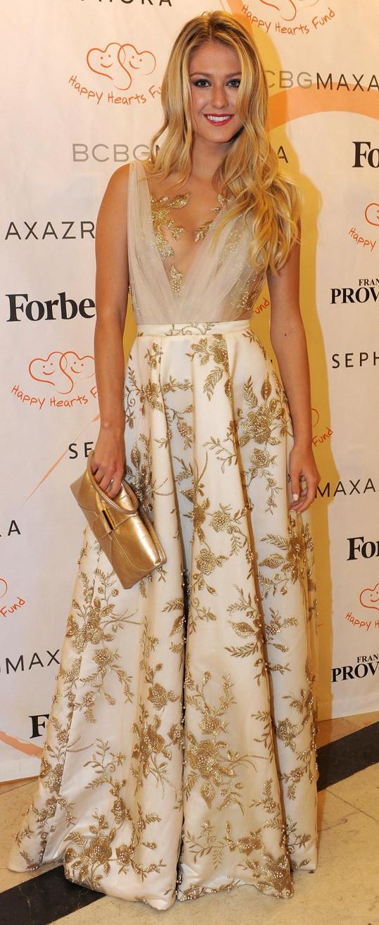 Česká Miss World 2015 Natálie Kotková plnila během večera úlohu reportérky Fashion TV. Zlatavá róba Poner, jejíž krajkové aplikace rafinovaně zakrývaly intimní partie nositelky, skvěle ladila s prostředím paláce Žofín.