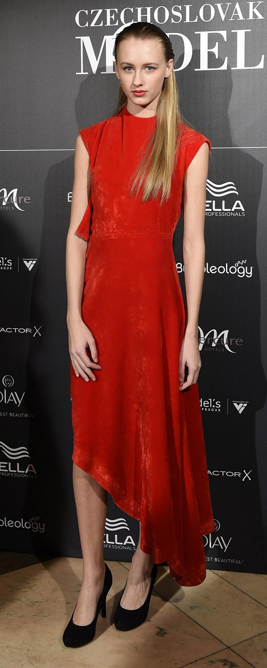Loňská vítězka soutěže Nikola Krůželová oblékla rudou róbu z veluru značky Chatty, které dominovala netradičně střižená zkosená sukně.