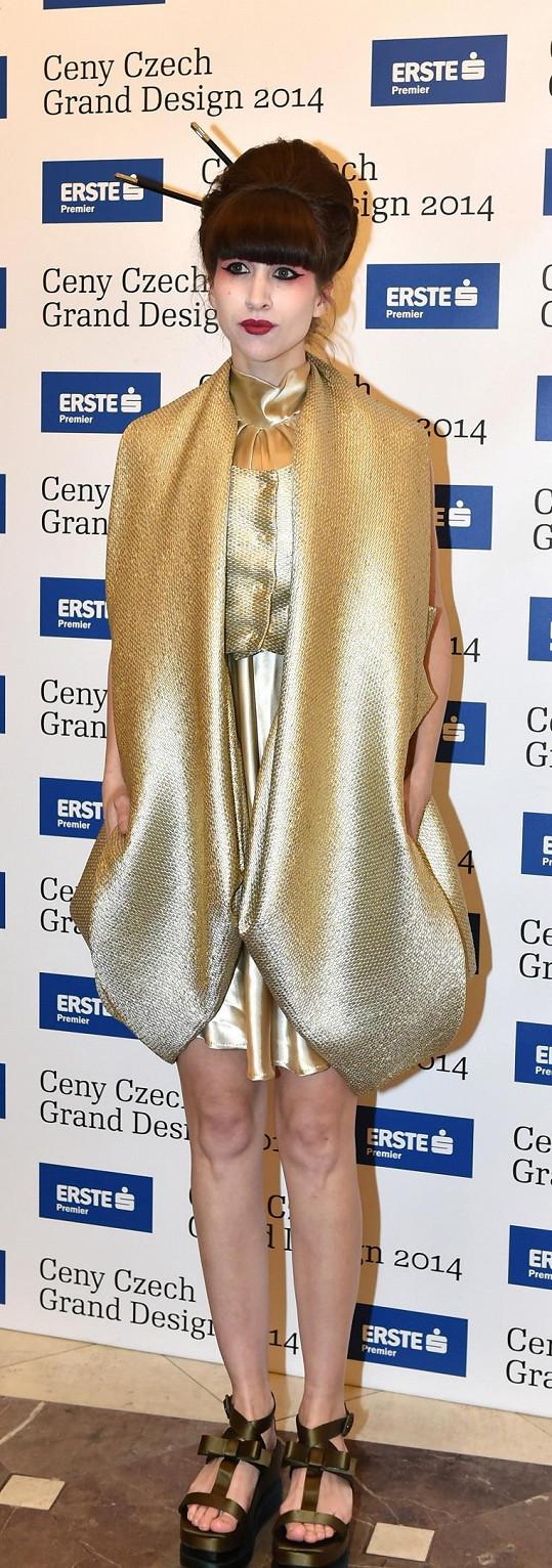 Bloggerka Ina Tina se oblékla zcela ve stylu večera, který byl inspirovaný Japonskem. V archivu Liběny Rochové vybrala tento výrazný zlatý model, který sladila se svými originálními sandály na platformě Prada. Make-up a vlasový styling pak vtipně připomínal japonskou gejšu.