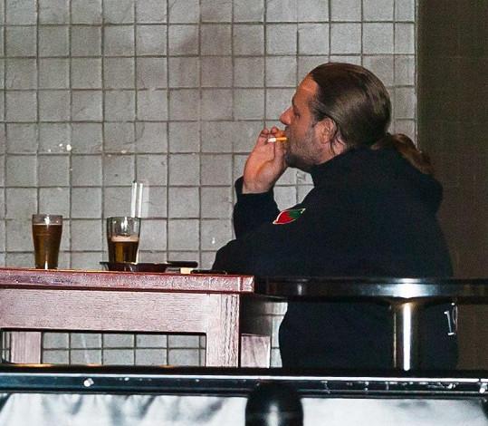 V hospodě si vychutnával pivo a cigaretu.