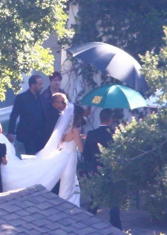 Nevěsta oblékla úzké bílé šaty s vlečkou a závojem.