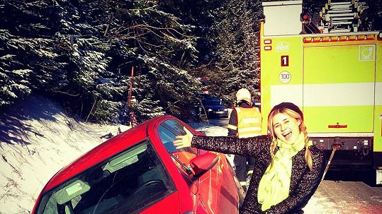 Elis a její auto v závěji, hasiči v pozadí.