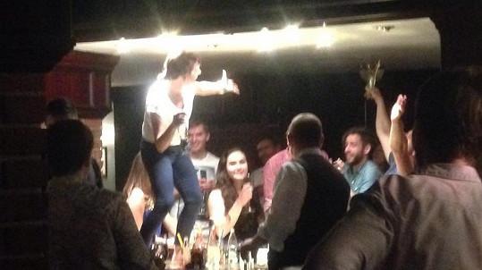Tatiana Vilhelmová řádí na baru, vzadu se směje Vojta Dyk.
