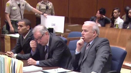 Chris Brown (sedící vlevo) u soudu v pozadí s Rihannou.