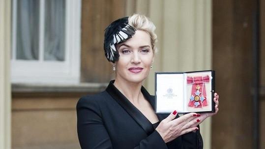 Kate Winslet pyšně třímá medaili.