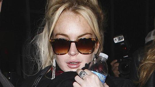 Průšvihářka Lindsay Lohan na veřejnosti pije vodu, ve svém domě si však i přes zákaz dopřává alkohol.