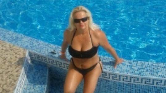 Monika v plavkách u hotelového bazénu