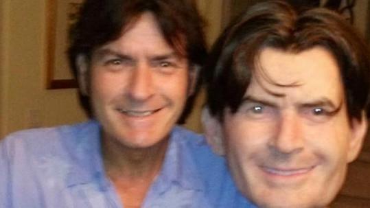 Pobavený Charlie Sheen ukazuje masku svého vlastního obličeje.