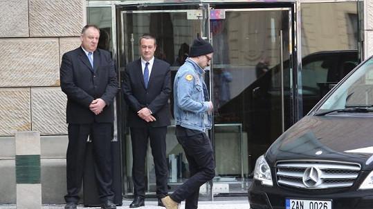 Justin vychází z hotelu.